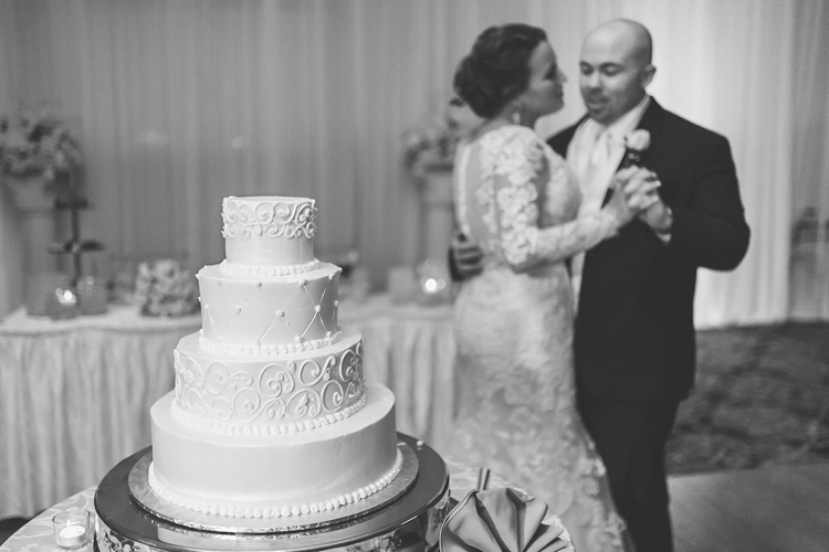 Tara and Dom cutting and slow dancing behind their wedding cake at Crystal Ballroom, NJ photography by NY NJ Wedding Photographers Pearl Paper Studio.