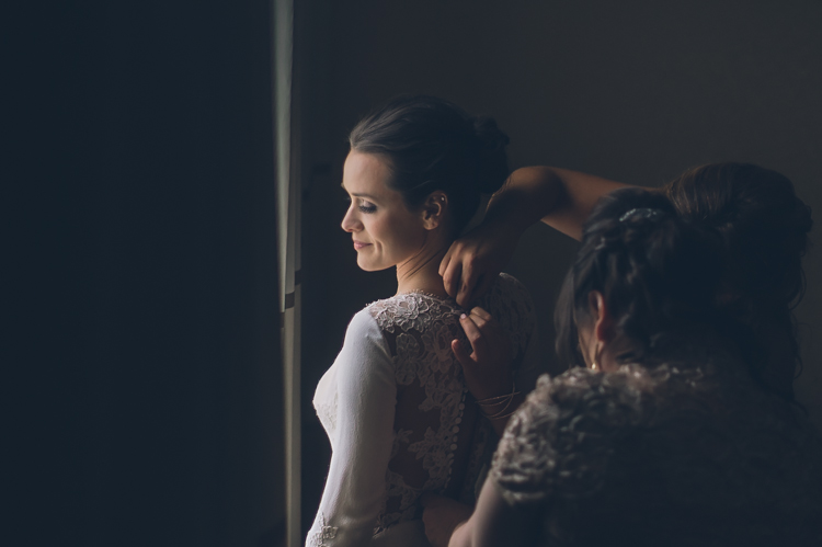 Tara putting on her wedding dress for her wedding at The Estate at Florentine Gardens, NJ photography by NY NJ Wedding Photographers Pearl Paper Studio.