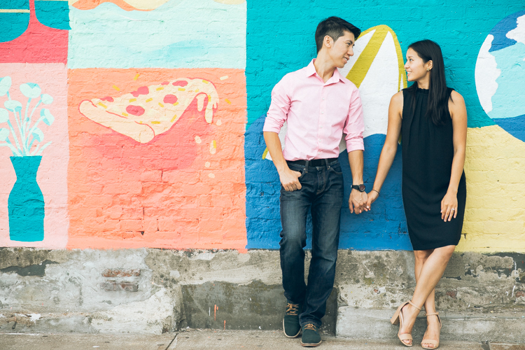 Waterfront Long Island City NY engagement session with Angela and Kingman. Angela and Kingman against colorful wall mural, New York City Skyline and industrial Long Island City as backdrop enjoyed looking at each other and laughing together during this fun engagement session with Edmund captured by Edmund from Pearl Paper Studio. We are New Jersey, New York and Long Island wedding photographers and our passion is to photograph fun, warm and energetic couples on their wedding day. We love to hear about your wedding day, and we would be thrilled to be part of it.