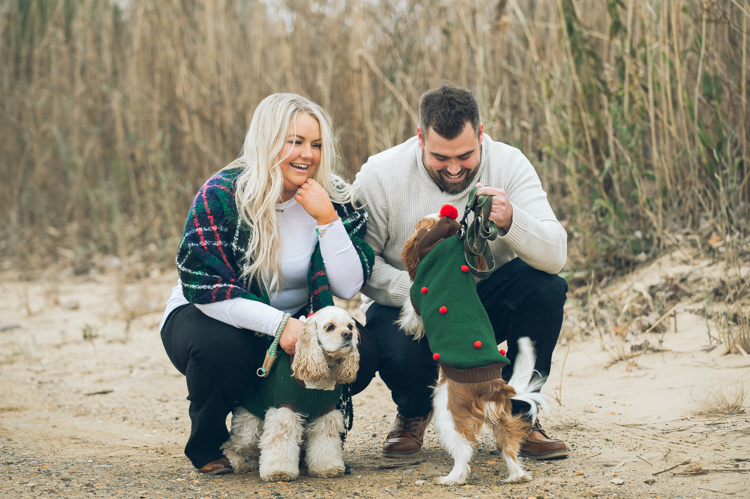 Cozy home session with Christie and Jay along with their two fur babies all dolled up in their holiday clothing! We love when our clients bring out their fur babies for their engagement session. Christie and Jay had the perfect idea for their engagement session which did not involve too much planning instead they focused on them and the photos came out fabulous. Christie and Jay just walked around their neighborhood in Keyport, NJ. Took a stroll along the winter ocean enjoying the brisk air, ocean, sand and then warmed up at their home w their pups. Christie and Jay's home engagement session captured by Steve from Pearl Paper Studio. Pearl Paper Studio wedding photography studio covering New Jersey, New York and Long Island brides and our passion is to photograph fun, warm and energetic couples on their very special wedding day.